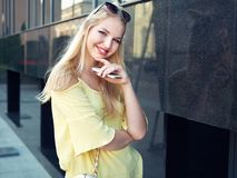 Young beautiful blonde woman with multi colored eyes high bun hairstyle jeans shorts yellow blouse enjoying warm evening posing ag. Ainst city building wall royalty free stock image