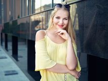 Young beautiful blonde woman with multi colored eyes high bun hairstyle jeans shorts yellow blouse enjoying warm evening posing ag. Ainst city building wall stock images