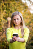 Young beautiful blonde woman offering a cup of Royalty Free Stock Photography