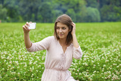 Young beautiful blonde woman photographing themselves on a cell Stock Photo