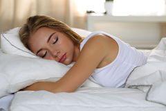 Young beautiful blonde woman portrait lying in bed sleeping Royalty Free Stock Image