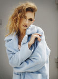 Young beautiful blonde woman posing in blue coat outdoors stock image