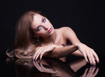 Young beautiful blonde woman sitting at mirror table on black ba Royalty Free Stock Photos