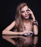 Young beautiful blonde woman sitting at mirror table on black ba Stock Photo