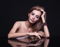 Young beautiful blonde woman sitting at mirror table on black ba Royalty Free Stock Images