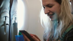 Young beautiful blonde woman sitting near the window in plane and using the smartphone. Couple traveling together. Man and woman talking, discussing the trip stock footage