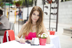 Young beautiful blonde woman sitting in a summer restaurant Royalty Free Stock Images