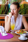 Young beautiful blonde woman sitting in a summer restaurant Stock Images
