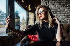 Young beautiful blonde woman taking a selfie in coffee shop. Hipster, red lips, glasses. stock photos