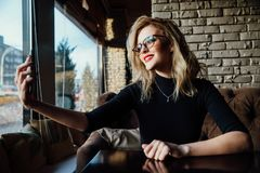 Young beautiful blonde woman taking a selfie in coffee shop. Hipster, red lips, glasses. stock photography