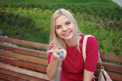 Young beautiful blonde woman with trendy bright makeup in fuchsia blouse pose faces doing a closeup selfie portraits sitting on th Royalty Free Stock Image