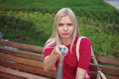 Young beautiful blonde woman with trendy bright makeup in fuchsia blouse pose faces doing a closeup selfie portraits sitting on th Royalty Free Stock Photos