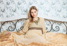 Young beautiful blonde woman in vintage hippie dress posing on the bed. Young beautiful blonde woman in vintage  dress posing on the bed Royalty Free Stock Photos
