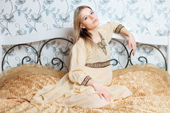 Young beautiful blonde woman in vintage hippie dress posing on the bed Stock Photography