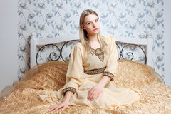 Young beautiful blonde woman in vintage hippie dress sitting on the bed Stock Photography