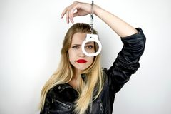 Free Young Beautiful Blonde Woman Wearing Black Leather Jacket Looks Desperate Having Handcuffs On One Hand On Isolated White Stock Photos - 154896743