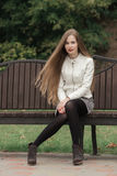 Young beautiful blonde woman in white leather jacket with extra long straight hair bright red lipstick posing on park bench Stock Images