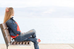 Young beautiful blondie woman sitting bench near sea. Young blondie pretty beautiful woman jeans sitting bench, sea beach view, Dead sea Israel Stock Image