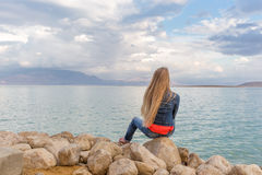 Young beautiful blondie woman sitting stones sea beach. Young blondie pretty beautiful woman jeans sitting stones back view, sea beach, Dead sea Israel Royalty Free Stock Photos
