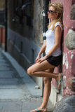 Young beautiful blondie woman standing against the wall in the old town. Travel. Royalty Free Stock Photos