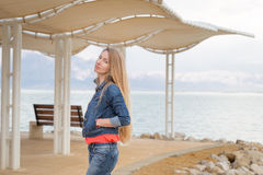 Young beautiful blondie woman standing sea beach shore. Beautiful young blondie woman standing sea beach, posing, wearing jeans, Dead sea Israel Stock Photography