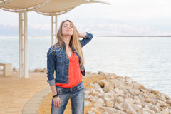 Young beautiful blondie woman standing sea beach shore. Beautiful young blondie woman standing sea beach, posing, wearing jeans, Dead sea Israel Royalty Free Stock Image
