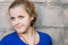 Young Blue-Eyed Girl. Young Beautiful Blue-Eyed Girl Near Brick Wall Royalty Free Stock Images