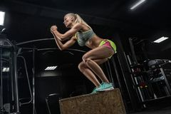 Young beautiful bodybuilding girl doing exercises in a modern gym. Blonde. Training crossfit. Jumping Concept - royalty free stock image