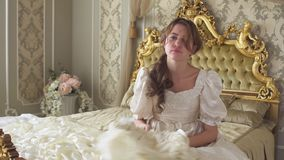 Young bored woman in ball gown and hat sitting on the huge golden bed and throw hat on the floor. Young beautiful bored woman in white medieval era dress and hat stock video footage