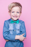 Young beautiful boy with blue shirt and butterfly tie. Studio portrait over pink background. Royalty Free Stock Photography