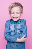 Young beautiful boy with blue shirt and butterfly tie. Studio portrait over pink background. Stock Images