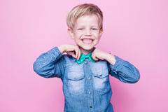 Young beautiful boy with blue shirt and butterfly tie. Studio portrait over pink background. Stock Photography