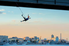 Young beautiful brave woman roupejumping in the evening. On the bridge Stock Photos