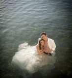 Young beautiful bridal couple having fun together at the beach. In body of water Stock Photos