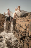 Young beautiful bridal couple having fun together at the beach. Near small water fall Stock Photos