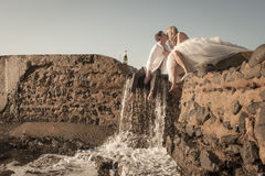 Young beautiful bridal couple having fun together at the beach. On a rock wall with champagne Royalty Free Stock Photos