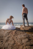 Young beautiful bridal couple having fun together at the beach. On rocks Royalty Free Stock Image