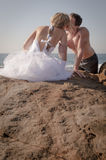 Young beautiful bridal couple having fun together at the beach. On rocks Royalty Free Stock Photo