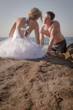Young beautiful bridal couple having fun together at the beach. Sitting on rocks Stock Photos
