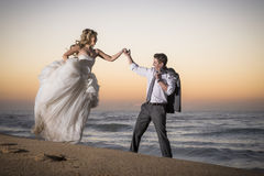 Young beautiful bridal couple having fun together at the beach. At sunrise Royalty Free Stock Image