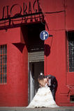 Young beautiful bridal couple kissing against red building Stock Images
