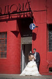 Young beautiful bridal couple leaning against red building Royalty Free Stock Image