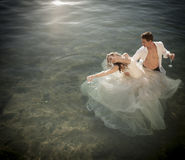 Young beautiful bridal couple outdoors in rock pool. Young beautiful bridal couple dancing playfully outdoors in rock pool Royalty Free Stock Photography