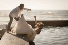 Young beautiful bridal couple outdoors on rock wall Royalty Free Stock Photos