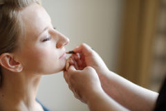 Young beautiful bride applying wedding make-up Royalty Free Stock Images