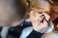 Young beautiful bride applying wedding make-up Stock Images