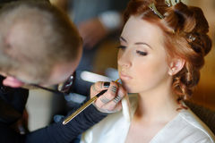 Young beautiful bride applying wedding make-up Royalty Free Stock Photo