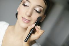 Young beautiful bride applying wedding makeup Royalty Free Stock Image