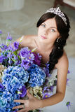 Young beautiful bride with a big bouquet of blue flowers Royalty Free Stock Photography