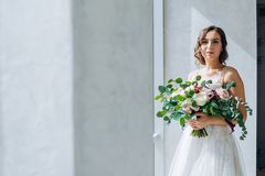 Bride with a wedding bouquet of white roses in hands. royalty free stock photos